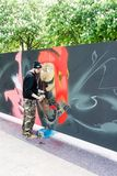 Grafittikonstnär som besprutar väggen Royaltyfri Bild
