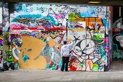 Grafittikonstnär Spraying Paint på väggen Royaltyfria Foton