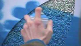 Grafittikonstn?r i gatan som g?r konst genom att anv?nda sprutm?lningsf?rg och stencilen Stencilgatakonst, stads- kultur stock video