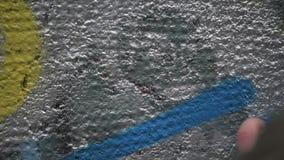 Grafittikonstn?r i gatan som g?r konst genom att anv?nda sprutm?lningsf?rg p? betongv?ggen Gatakonst, stads- kultur stock video