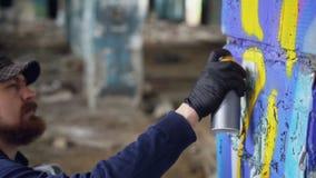 Grafittimålaren squatting nära kolonn i gamla tomma byggnads- och målninggrafitti med att skapa för sprutmålningsfärg stock video