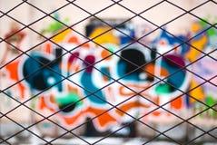 Grafittis abstratos através da cerca das barras de metal Imagem de Stock Royalty Free