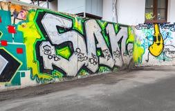 Grafittis caóticos coloridos pintados sobre a cerca velha Fotos de Stock