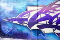 Grafittis coloridos em uma parede de tijolo Fotos de Stock