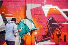 Grafittis criativos da pintura do artista em paredes Imagens de Stock Royalty Free
