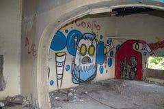 Grafittis da parede dentro da construção antiga fotografia de stock