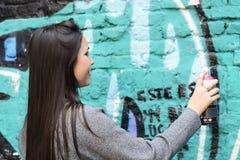 Grafittis do desenho da mulher com pintura à pistola na parede da rua aint na parede da rua outdoors Conceito urbano Foto de Stock