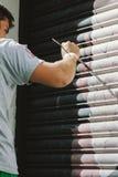 Grafittis do menino, pintados com escova, nas cortinas de uma loja Foto de Stock Royalty Free