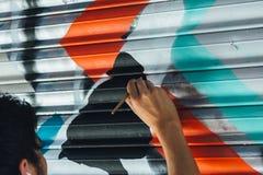 Grafittis do menino, pintados com escova, nas cortinas de uma loja Fotografia de Stock