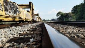 Grafittis em carros de trem em trilhas imagem de stock