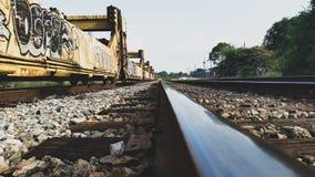Grafittis em carros de trem em trilhas imagens de stock