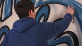 Grafittis masculinos do desenho do artista em uma parede com uma lata de pulverizador Foto de Stock Royalty Free