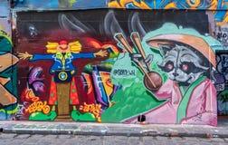 Grafittis ou pintura mural como o comentário político no trunfo e na China fotos de stock