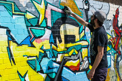 Grafittis urbanos do desenho do artista em uma parede em Shoreditch Imagem de Stock Royalty Free