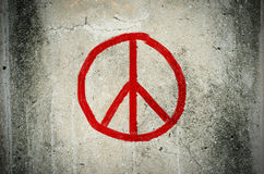Grafittis vermelhos do símbolo de paz na parede do ciment do grunge Fotos de Stock