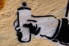 Grafittisprejcan som målas på en betongvägg Arkivbild
