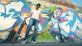 Grafittivägg och en ung man som lyfter hans skateboard med hans ben arkivfilmer