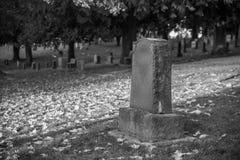 Grafsteen en graven in zwart-wit kerkhoflandschap, stock foto's