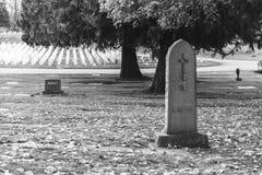 Grafsteen en graven in zwart-wit kerkhoflandschap, stock foto