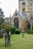 Grafstenen in begraafplaats met erachter kerk Verticale mening van memorandum Stock Foto