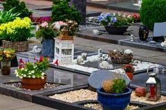 Grafstenen in een begraafplaats met vele verschillende bloemen Stock Afbeeldingen