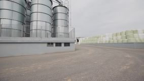 Grain bags and water tanks stay by each other at factory backyard