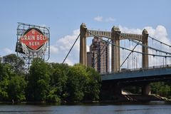 Grain Belt Beer sign and historic bridge above the Mississippi. Grain Belt Beer sign towers above the Mississippi River alongside an old historic bridge in royalty free stock image