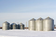Grain bins. Six grain bins on a winter field Royalty Free Stock Images