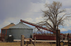 Grain bins and auger. Grain auger on a farm Royalty Free Stock Images