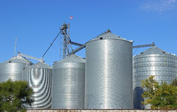 Grain Bins. A cluster of grain bins at a rural elevator with a bright blue sky stock photography