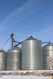 Grain Bins in Winter. In Iowa with blue sky royalty free stock photo