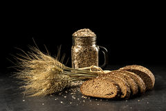 Grain bouquet, golden oats spikelets in jar on dark wooden table, buns and can filled with dried grains Stock Image