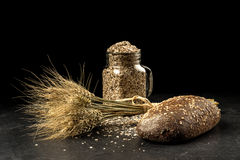 Grain bouquet, golden oats spikelets in jar on dark wooden table, buns and can filled with dried grains. Stock Photography