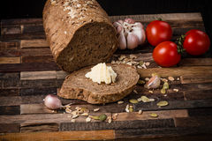 Grain bread. Grain bread and butter with tomatoes and garlic on old wooden background Stock Photo