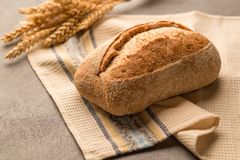 Grain bread with seeds and crunchy fragrant crust is on a towel stock photography