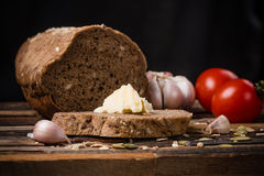 Grain bread. Sliced wheat bread with butter on an old wooden background Stock Photography
