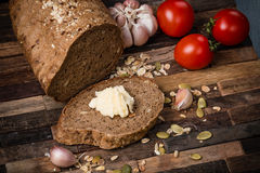 Grain bread. Sliced wheat bread with butter on an old wooden background Royalty Free Stock Image