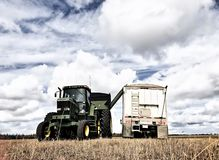 Grain cart unloading into a tractor trailer stock photography