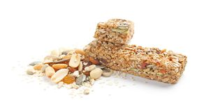 Grain cereal bars with nuts and raisins. On white background royalty free stock photo