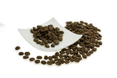 Grain coffee. Grain brown roasted coffee, lying on a white saucer and around Royalty Free Stock Photos