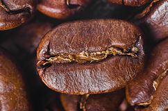 Grain of coffee by CU. On a background coffee grains Royalty Free Stock Image