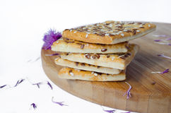 Grain cookies stacked on a wooden board with flowers. White background Stock Images