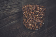 Grain de café à l'intérieur de sac zip-lock clair au fond en bois, couleur Photographie stock libre de droits