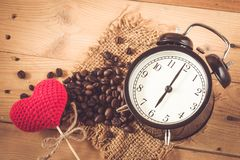 Grain de café avec l'horloge de matin de coeur d'amour sur le bois Photo libre de droits