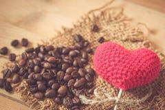 Grain de café avec le coeur d'amour sur le sac en bois Photos stock