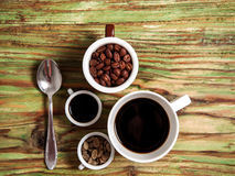Grain de café dans des tasses et la cuillère sur la table Photo stock