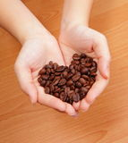 Grain de café dans la main Photo stock