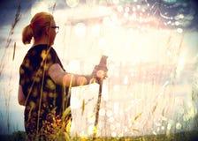 Grain de film La longue fille de cheveux marche par le champ de blé au fond d'or étonnant de coucher du soleil Image stock