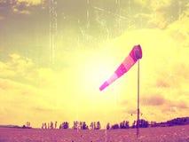 Grain de film Le jour chaud d'été sur l'aéroport de sport avec le manche à air abandonné, vent souffle et le manche à air se dépl Photographie stock libre de droits