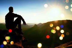 Grain de film Prise de randonneur détendant sur une roche et appréciant le coucher du soleil à l'horizon Photo stock